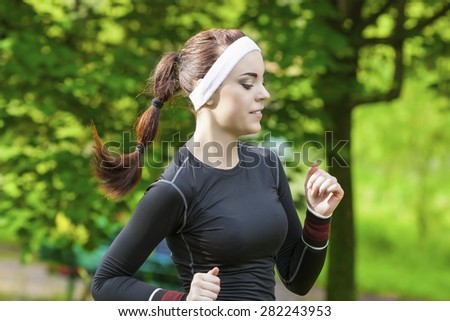 Portrait of Smiling Caucasian Sportswoman Having Her Regular Training Outdoors. Horizontal Image Orientation - stock photo