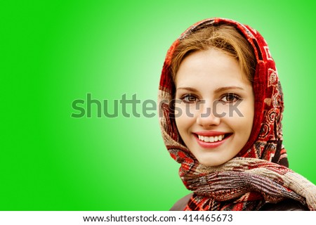 Portrait of smiling charming young woman in headscarf on a green background. - stock photo
