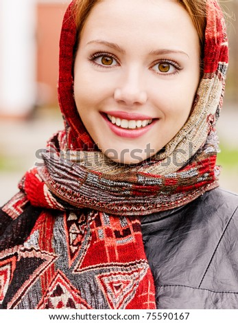 Portrait of smiling charming young woman in headscarf on city background. - stock photo