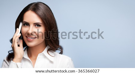 Portrait of smiling cheerful brunette businesswomen or customer support female phone operator with cell phone, against grey background, with blank copyspace area for slogan or text - stock photo