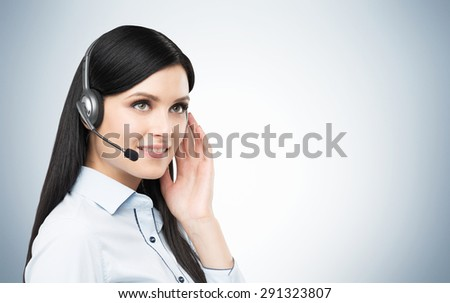 Portrait of smiling cheerful support phone operator in headset. Studio blue background. - stock photo