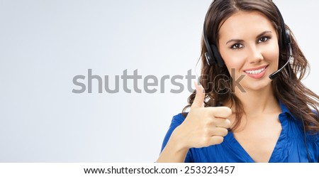 Portrait of smiling cheerful young support phone operator showing thumbs up gesture, with copyspace area - stock photo