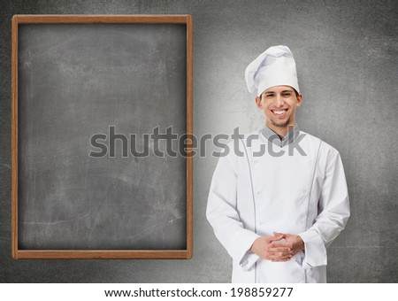 Portrait of smiling chef cook standing near grey menu blackboard, isolated on grey - stock photo
