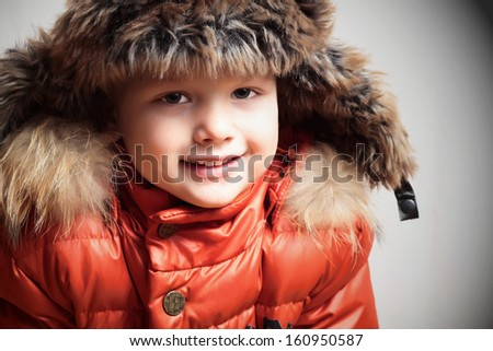 Portrait of smiling child in fur hood and orange winter jacket.fashion boy - stock photo