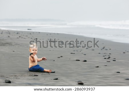 Portrait of smiling child sitting and playing alone with fun on balinese black sand sea beach before swimming Family lifestyle, water leisure during summer vacation with baby on tropical Bali island - stock photo