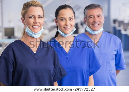 Portrait of smiling co-workers standing in a line in dental clinic - stock photo