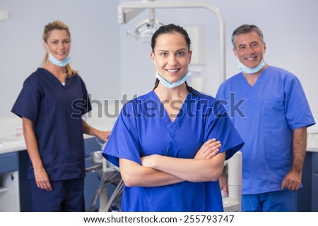 Portrait of smiling co-workers standing in dental clinic - stock photo
