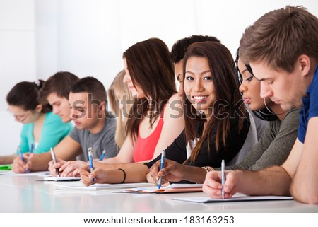 Portrait of smiling college student sitting with classmates writing at desk - stock photo