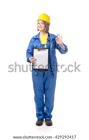 portrait of smiling construction female worker in yellow helmet and blue workwear holding blank clipboard and showing okay sign isolated on white background. proposing service. advertisement gesture - stock photo