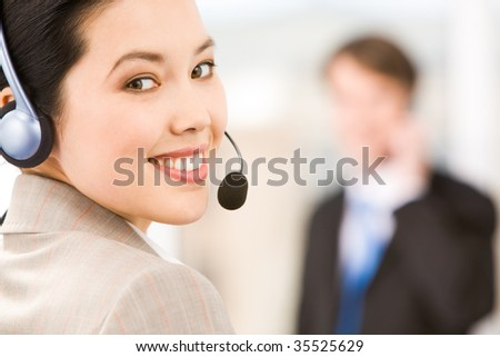 Portrait of smiling consultant with headset looking at camera - stock photo