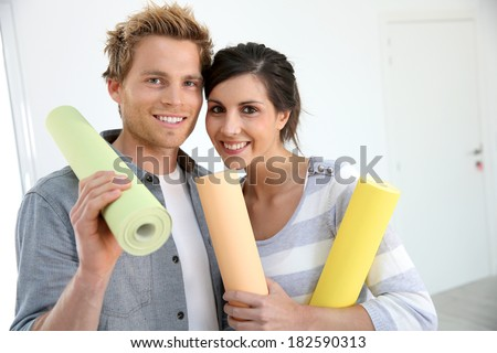 Portrait of smiling couple holding wallpaper rolls - stock photo