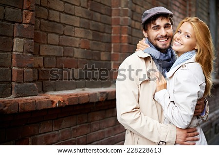 Portrait of smiling couple in stylish trench-coats looking at camera outside - stock photo