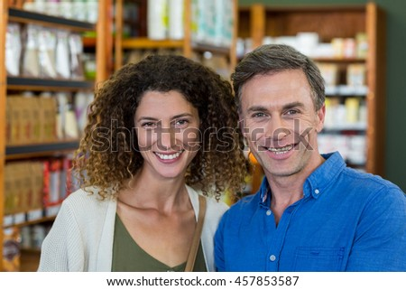 Portrait of smiling couple in supermarket - stock photo