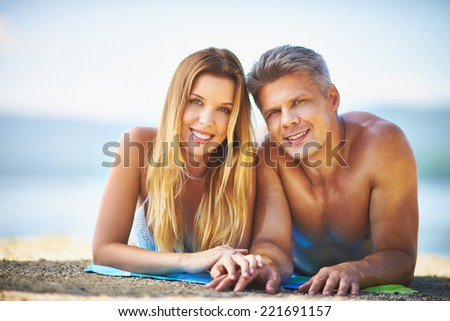 Portrait of smiling couple sunbathing in the beach - stock photo