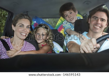 Portrait of smiling couple with two children in car - stock photo