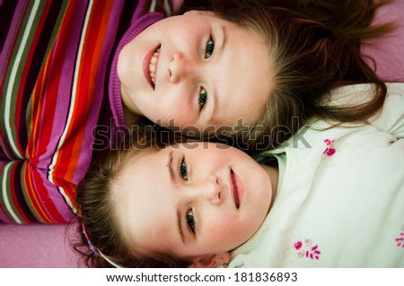 Portrait of smiling cute children (sisters) at home lying in bed - stock photo