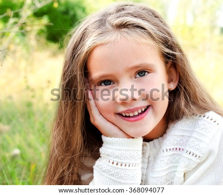 Portrait of smiling cute little girl in summer day outdoor - stock photo