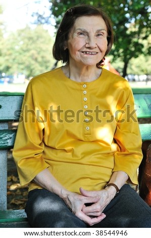 Portrait of smiling eighty-something senior woman sitting on bench outdoors in park - stock photo