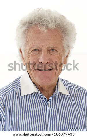 Portrait of smiling elderly man with white hair wearing striped shirt - stock photo