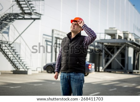 Portrait of smiling engineer in hardhat posing on construction site - stock photo