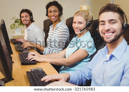 Portrait of smiling executives working together in call center - stock photo