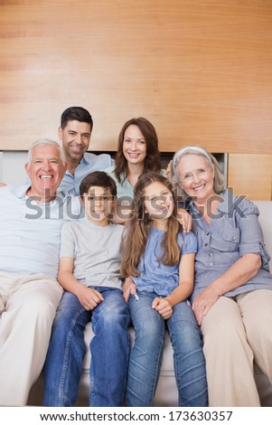 Portrait of smiling extended family sitting on sofa in the living room at home - stock photo
