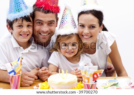 Portrait of smiling family celebrating son's birthday - stock photo