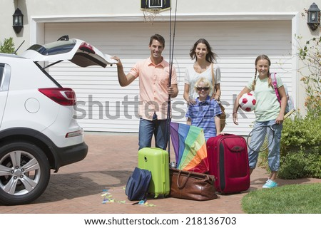 Portrait of smiling family packing car in sunny driveway - stock photo