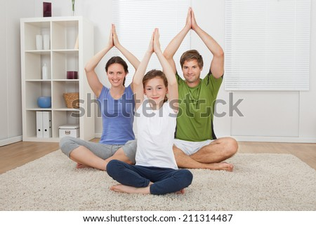 Portrait of smiling family practicing yoga on rug at home - stock photo