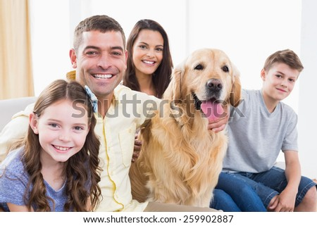 Portrait of smiling family sitting with Golden Retriever on sofa at home - stock photo