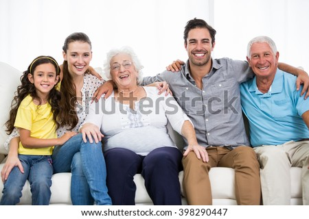Portrait of smiling family with arm around while sitting on sofa at home - stock photo
