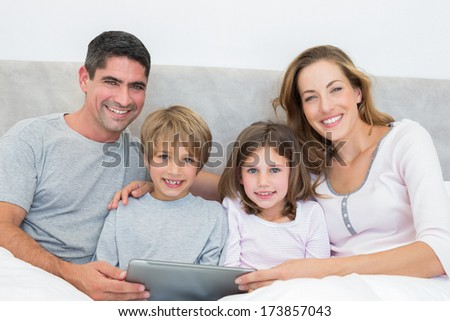 Portrait of smiling family with digital tablet in bed - stock photo