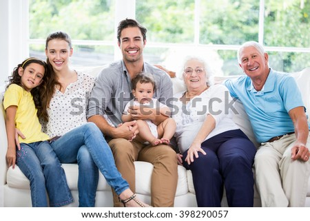 Portrait of smiling family with grandparents while sitting on sofa at home - stock photo