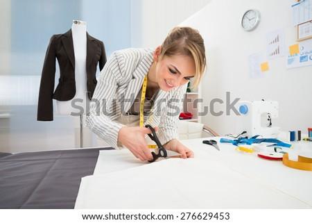 Portrait Of Smiling Fashion Designer Cutting Fabric In Studio - stock photo