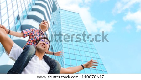Portrait of smiling father giving his son piggyback ride outdoors against sky and modern skyscraper building - stock photo