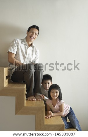 Portrait of smiling father sitting with children on wooden staircase - stock photo