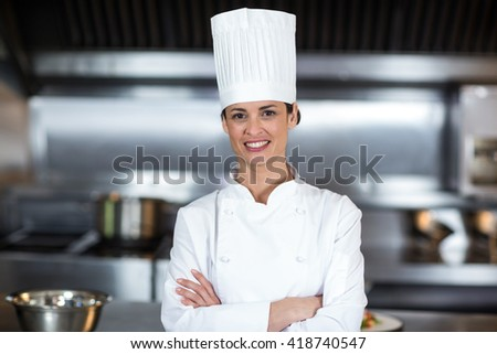 Portrait of smiling female chef with arms crossed standing in commercial kitchen - stock photo
