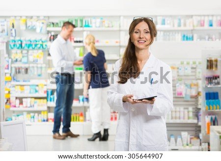 Portrait of smiling female chemist holding digital tablet while assistant and customer standing in background at pharmacy - stock photo