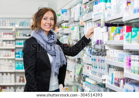 Portrait of smiling female consumer choosing product in pharmacy - stock photo