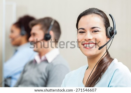 Portrait of smiling female customer service agent with colleagues in background at office - stock photo