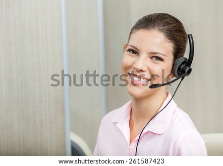 Portrait of smiling female customer service executive wearing headset in call center - stock photo