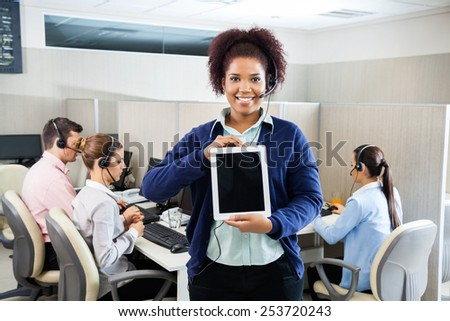 Portrait of smiling female customer service representative displaying tablet computer while colleagues working in background at call center - stock photo