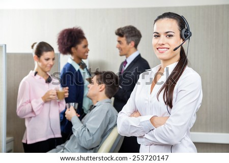 Portrait of smiling female customer service representative standing arms crossed while team discussing in background at call center - stock photo
