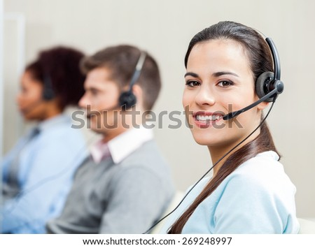 Portrait of smiling female customer service representative with colleagues in background at office - stock photo