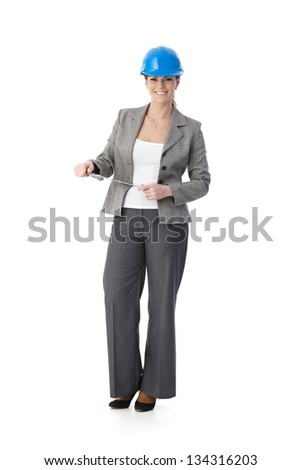 Portrait of smiling female engineer wearing protective hat, standing holding clipboard, looking at camera, cutout on white. - stock photo
