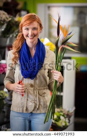 Portrait of smiling female florist trimming flower stem at flower shop - stock photo