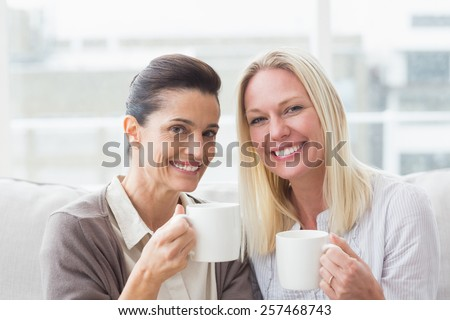 Portrait of smiling female friends having coffee in living room - stock photo