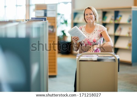 Portrait of smiling female librarian with trolley of books in library - stock photo