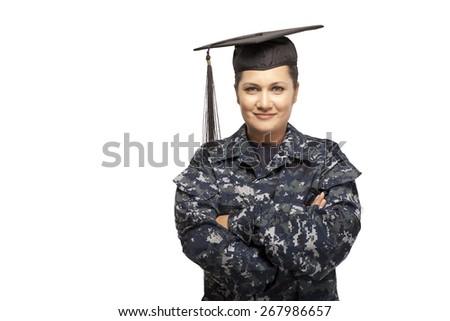 Portrait of smiling female navy sailor wearing graduation cap - stock photo