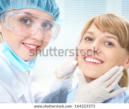 Portrait of smiling female patient  with dentist - stock photo